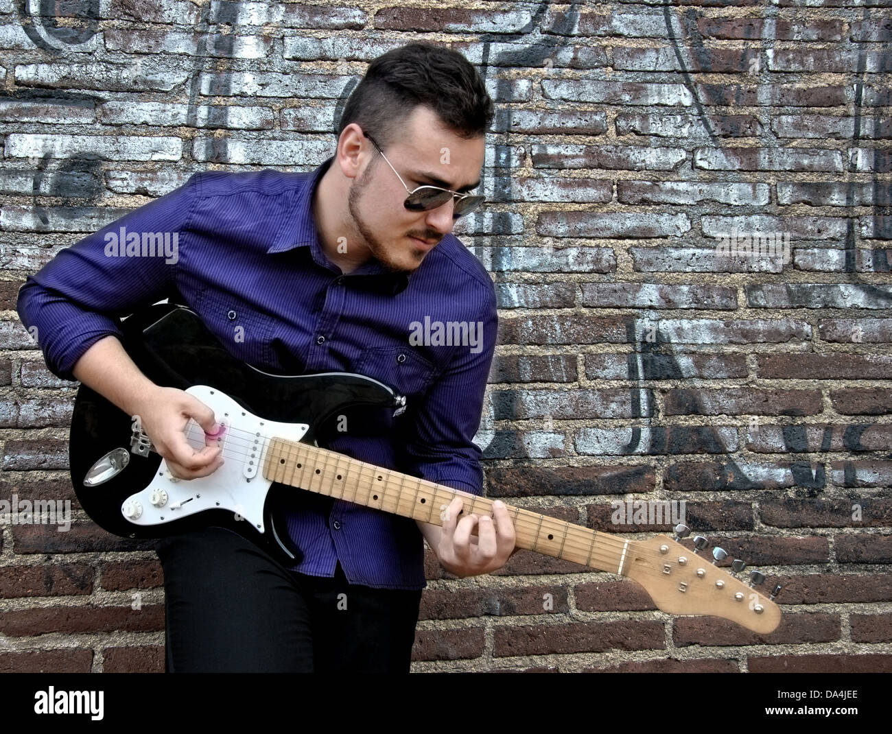 musician posing with his guitar in a wall of graffiti - Stock Image