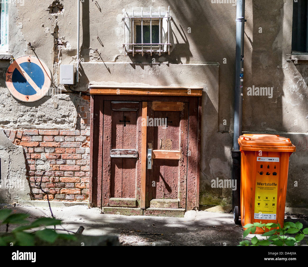 Urban decay - No entry sign, brick wall, dilapidated door and trash bin in an inner courtyard of aBuilding, Mitte, - Stock Image
