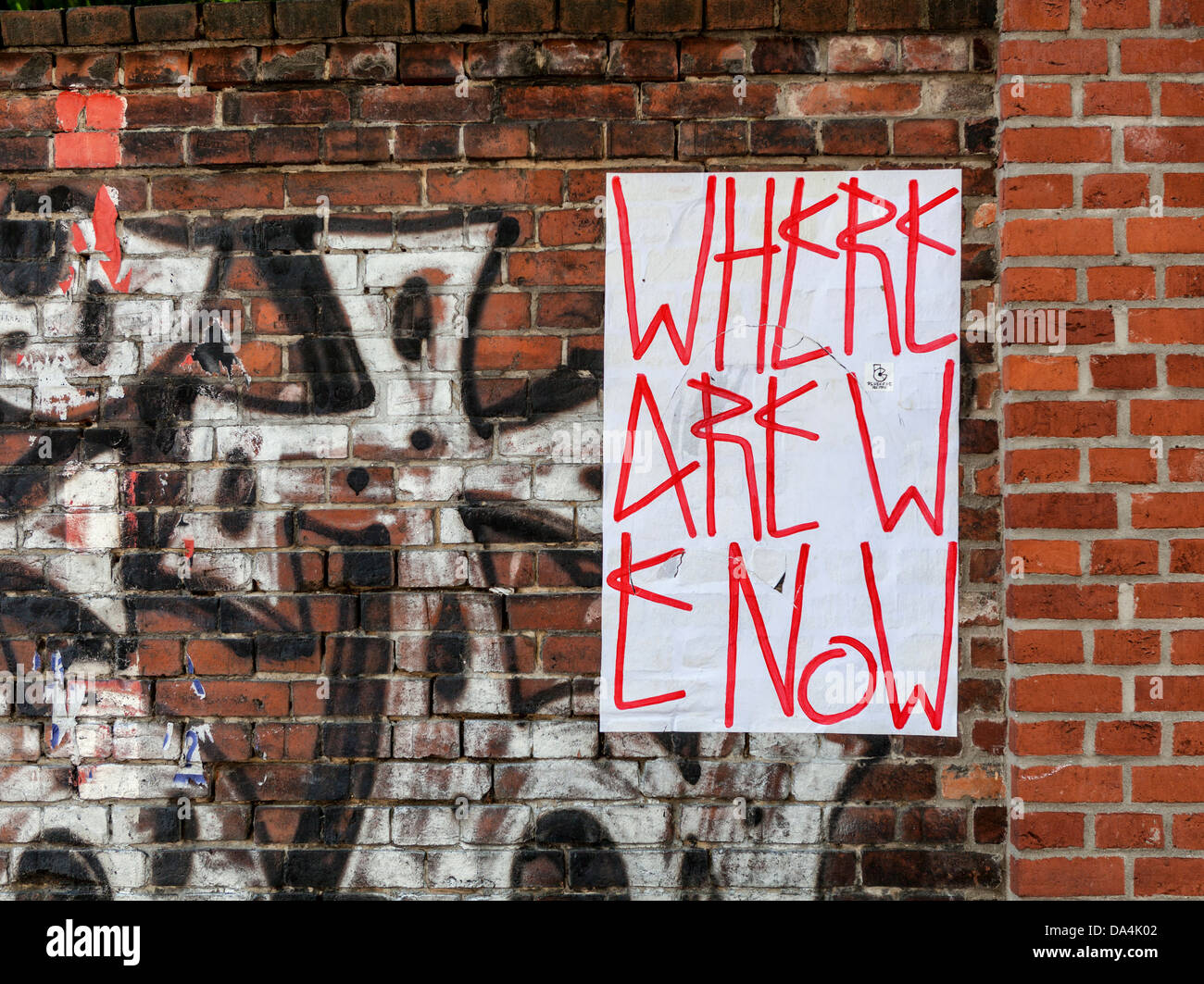 'where are we now' - a poster on a graffiti-covered brick wall, Mitte, Berlin - Stock Image
