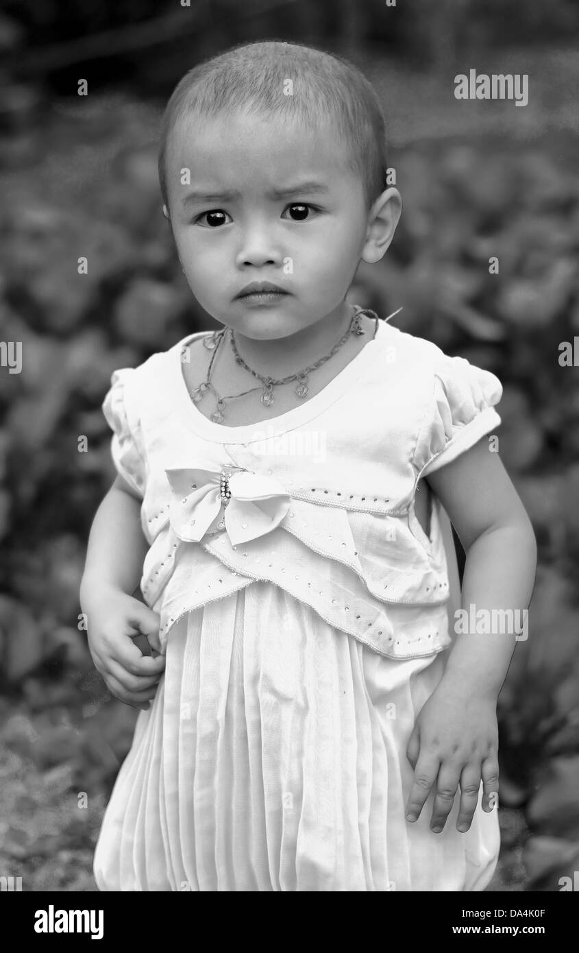 young burrmese sad, as her mother is away working in Thailand, girl in front of family vegetable garden - Stock Image
