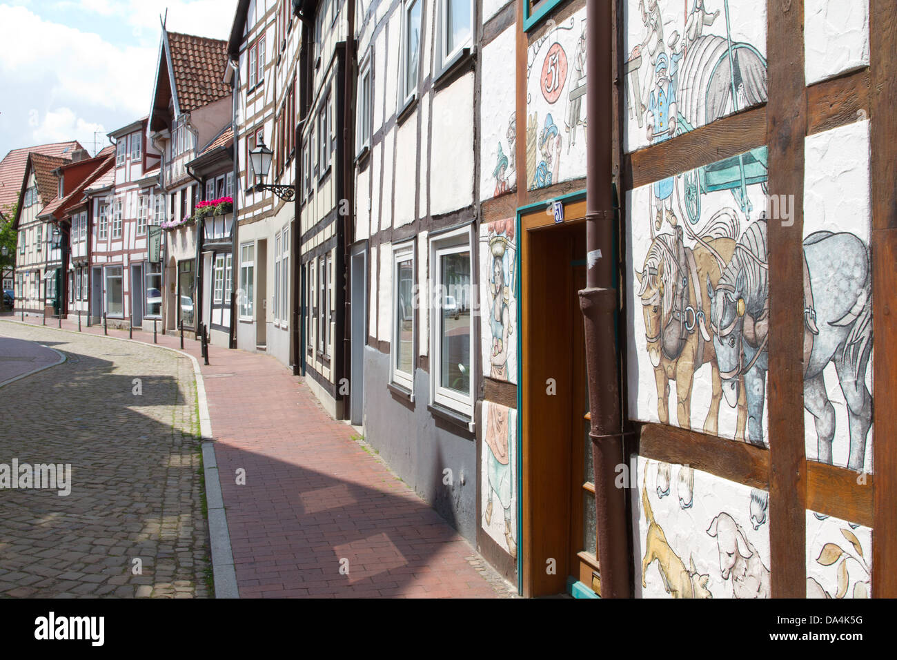 In an old cobbled street in Hameln/Hamlin a typically timbered building is finished with strong pictorial details - Stock Image