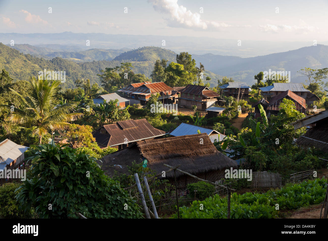 village with wooden huts and thatched roofs on a mountain slope in green jungle near Hpa An, Burma Stock Photo