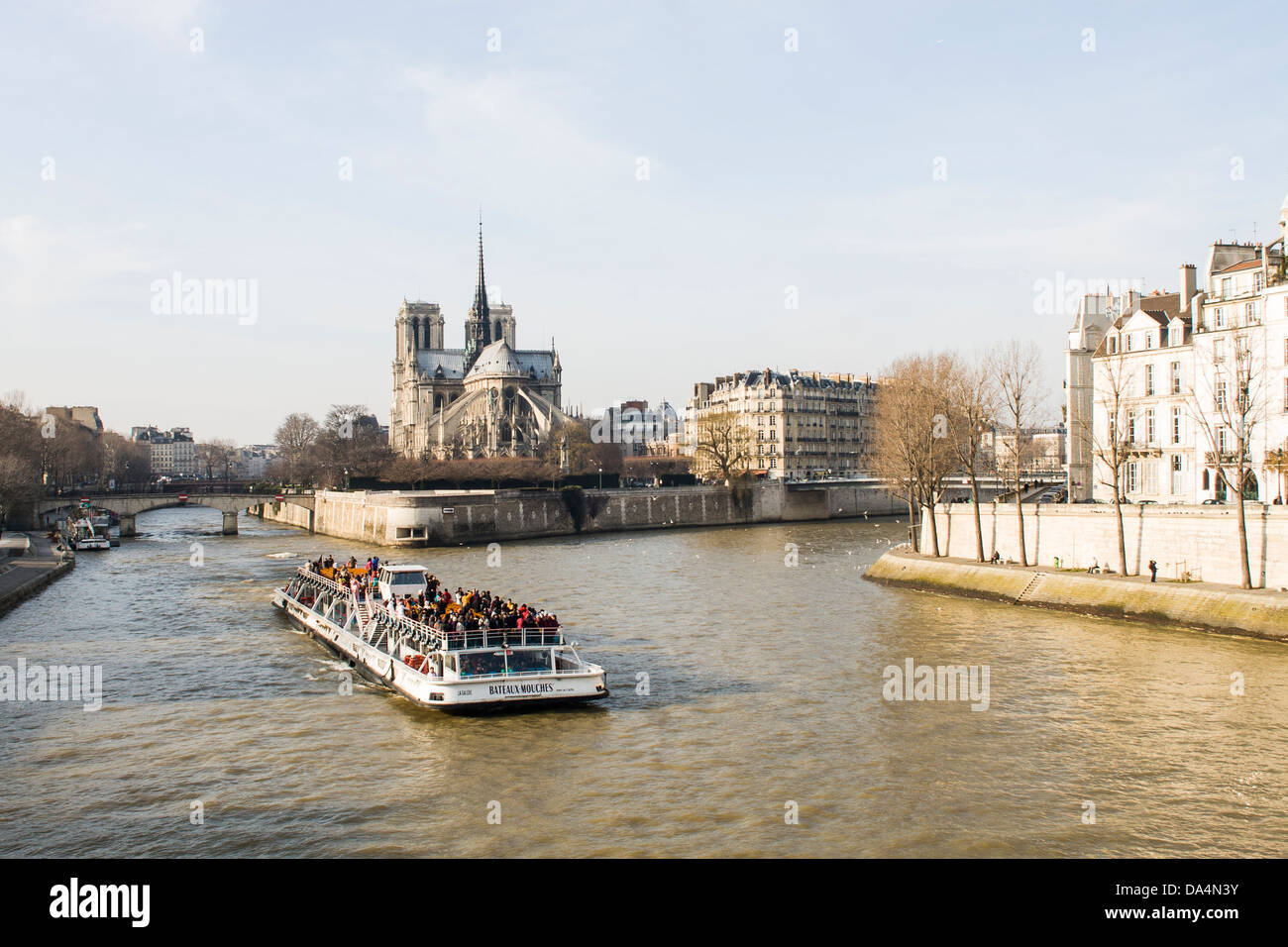 Tour boat on Seine River and Notre Dame Cathedral in the background. Paris, France. - Stock Image