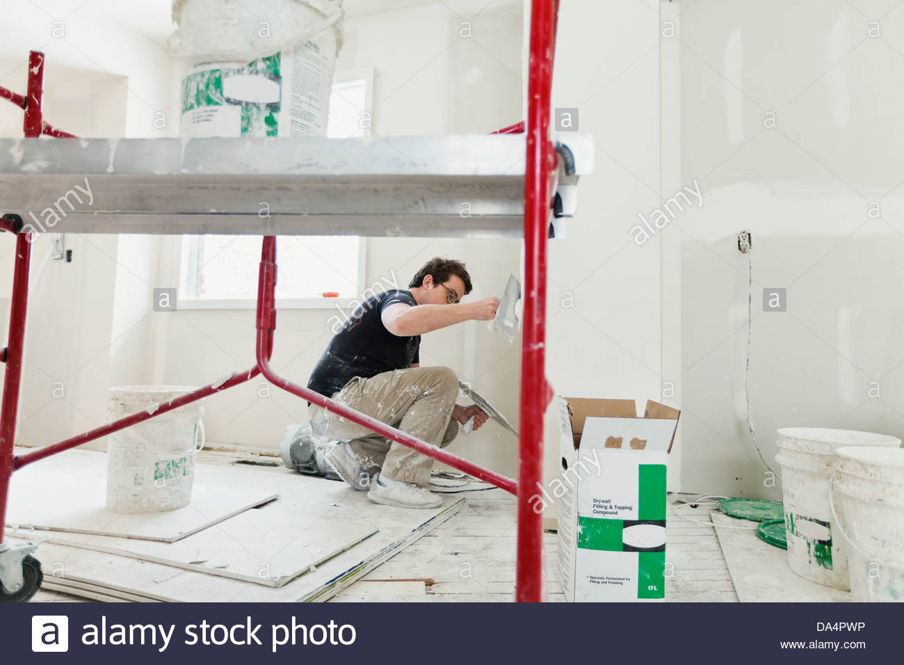 Tradesman plastering drywall with trowel in home Stock Photo