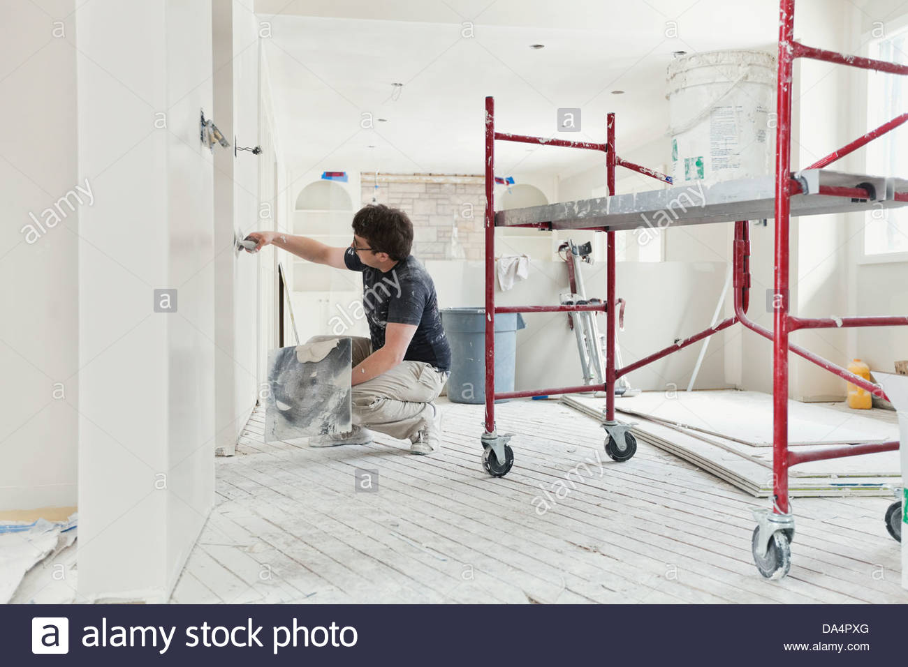 Tradesman plastering drywall with trowel in home - Stock Image