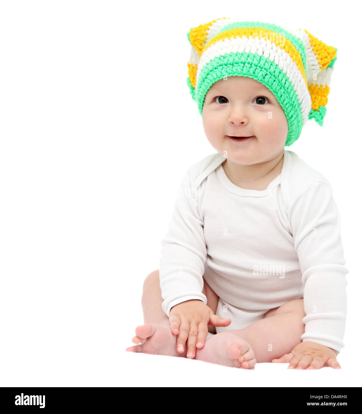 beautiful happy baby boy sitting on white bed - Stock Image