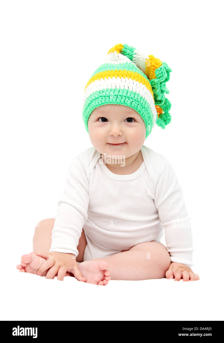 smiling baby sitting on bed - Stock Image