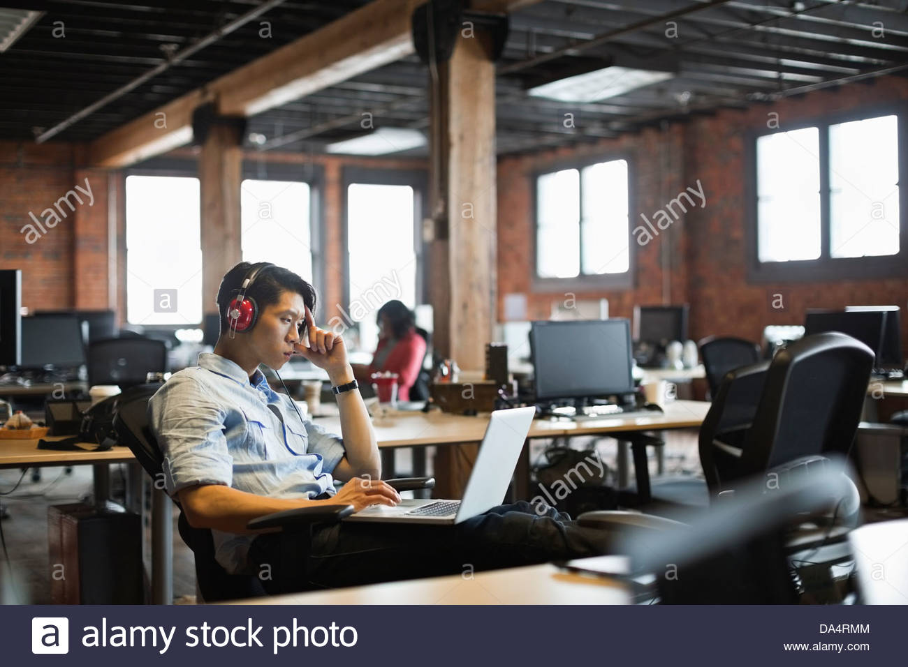 Entrepreneur working on laptop in creative office space - Stock Image