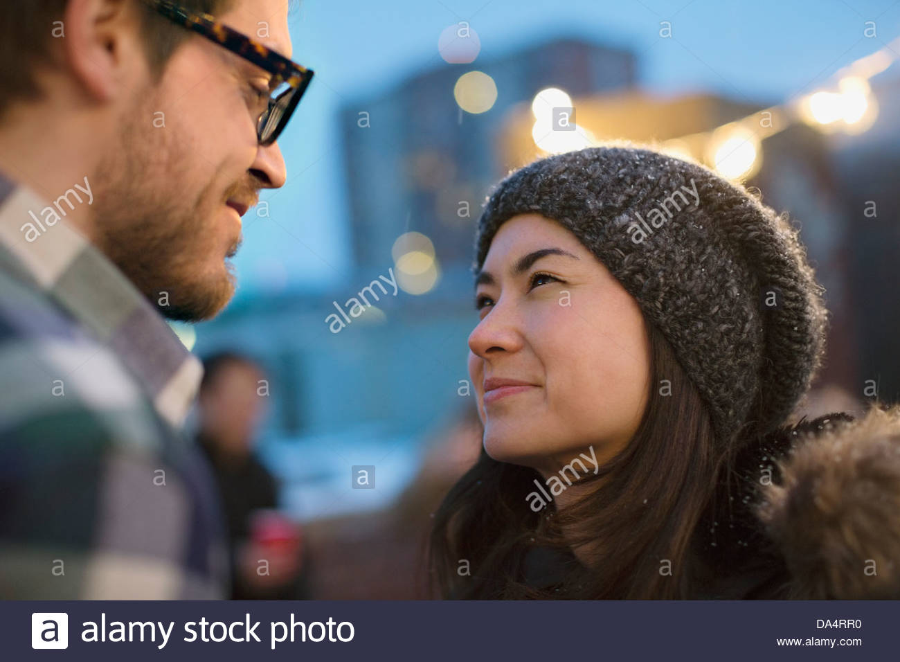Couple on rooftop celebrating with friends - Stock Image