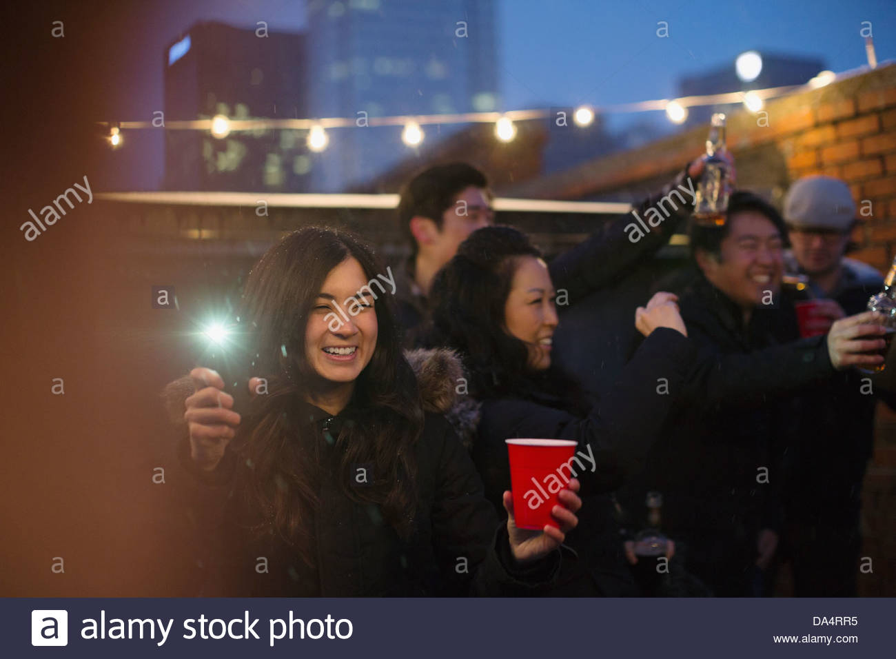 Group of entrepreneurs celebrating on rooftop - Stock Image