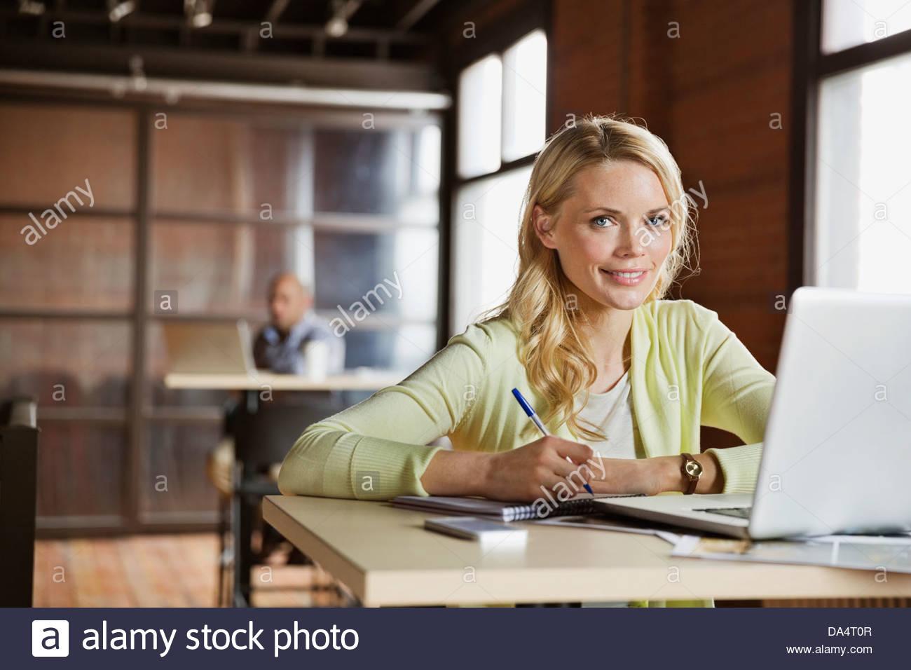 Portrait of female entrepreneur sitting at desk in office - Stock Image