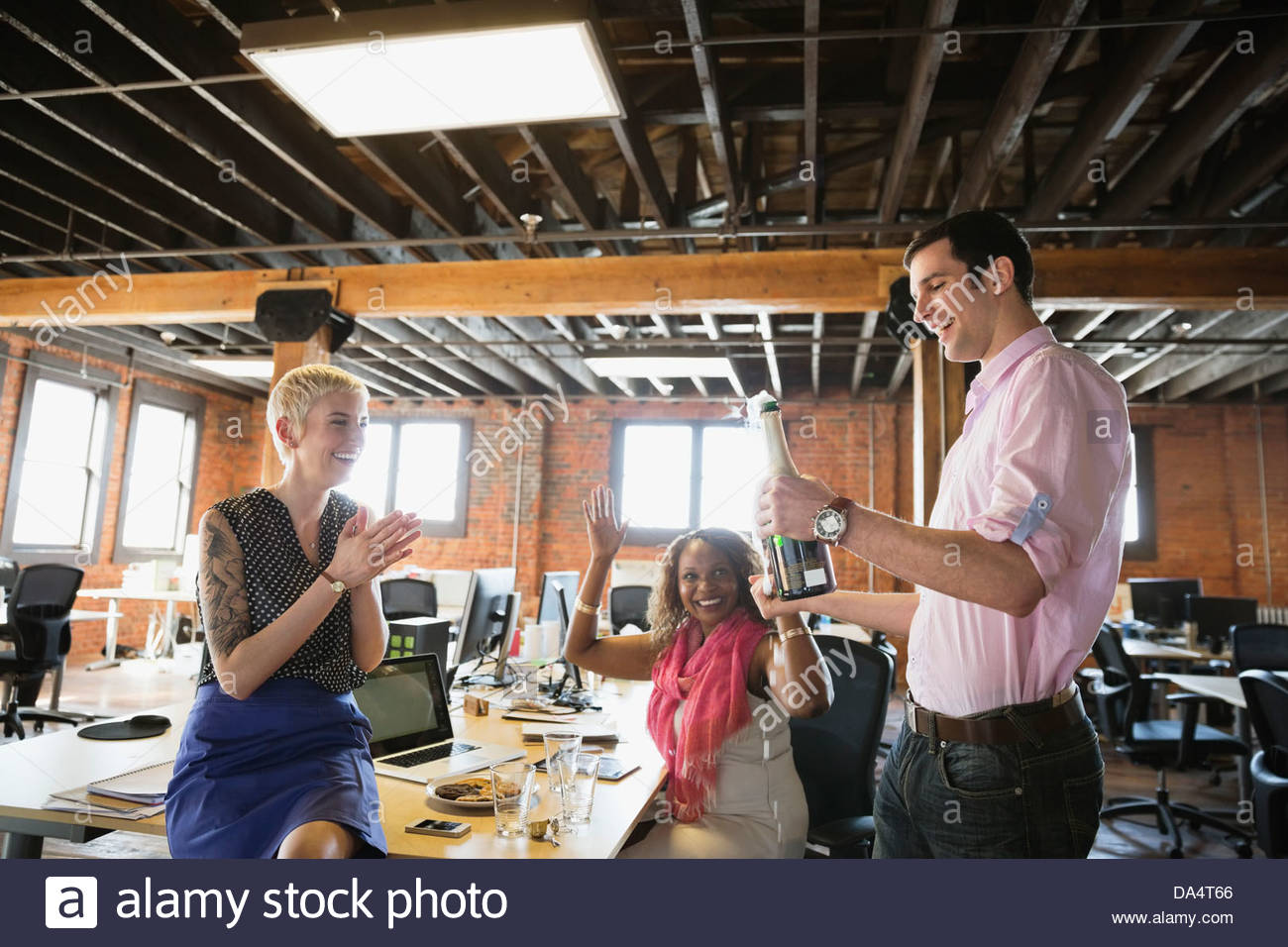 Entrepreneurs celebrating with champagne in office - Stock Image