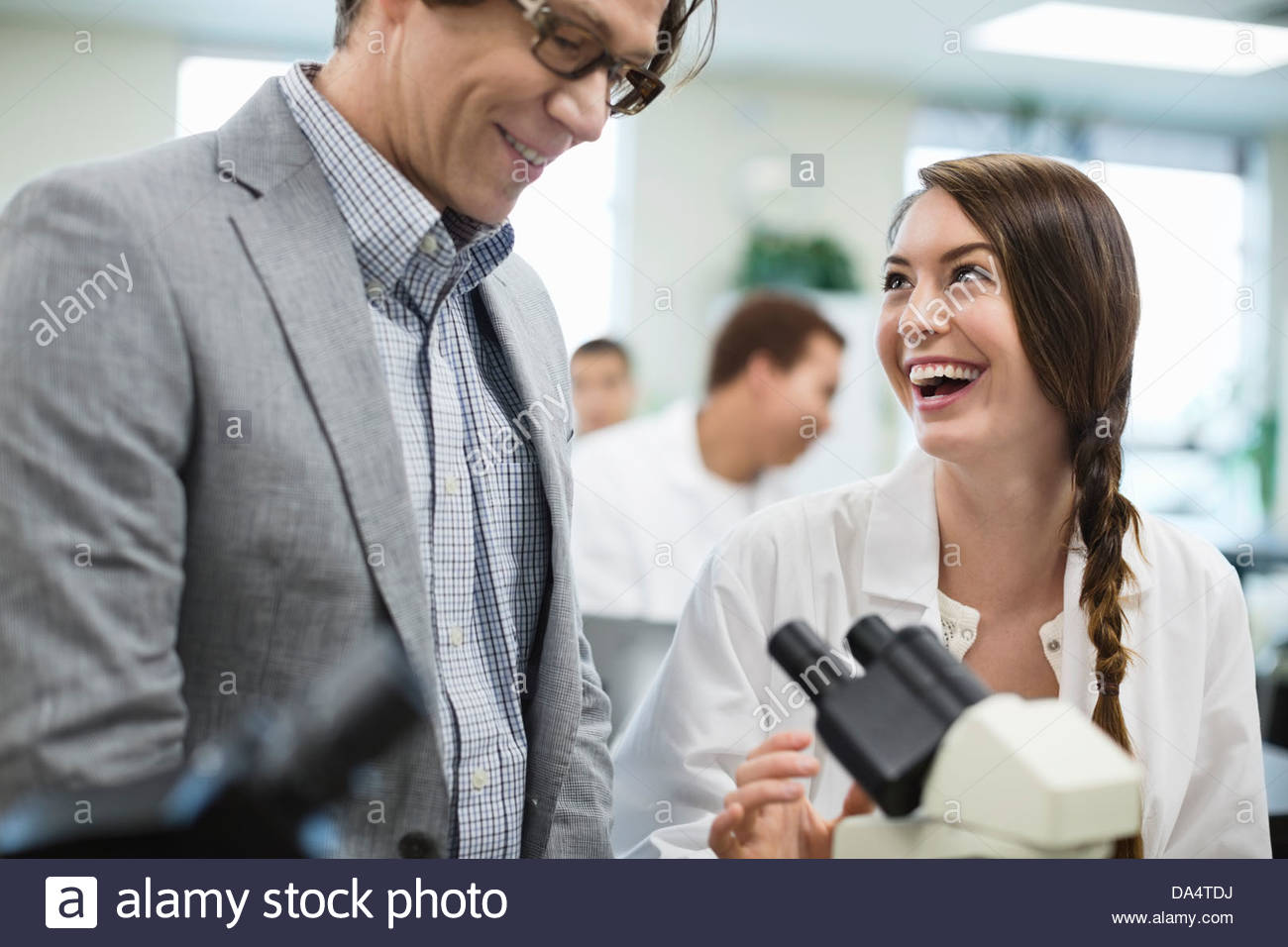 Female student looking at professor in college science lab - Stock Image
