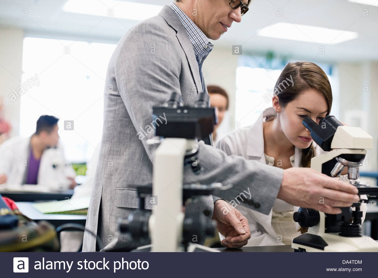 Professor helping female student with microscope in college science lab - Stock Image