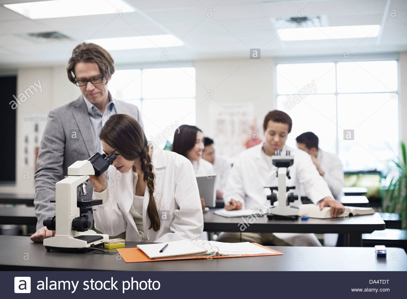 Professor helping female student in college science lab - Stock Image