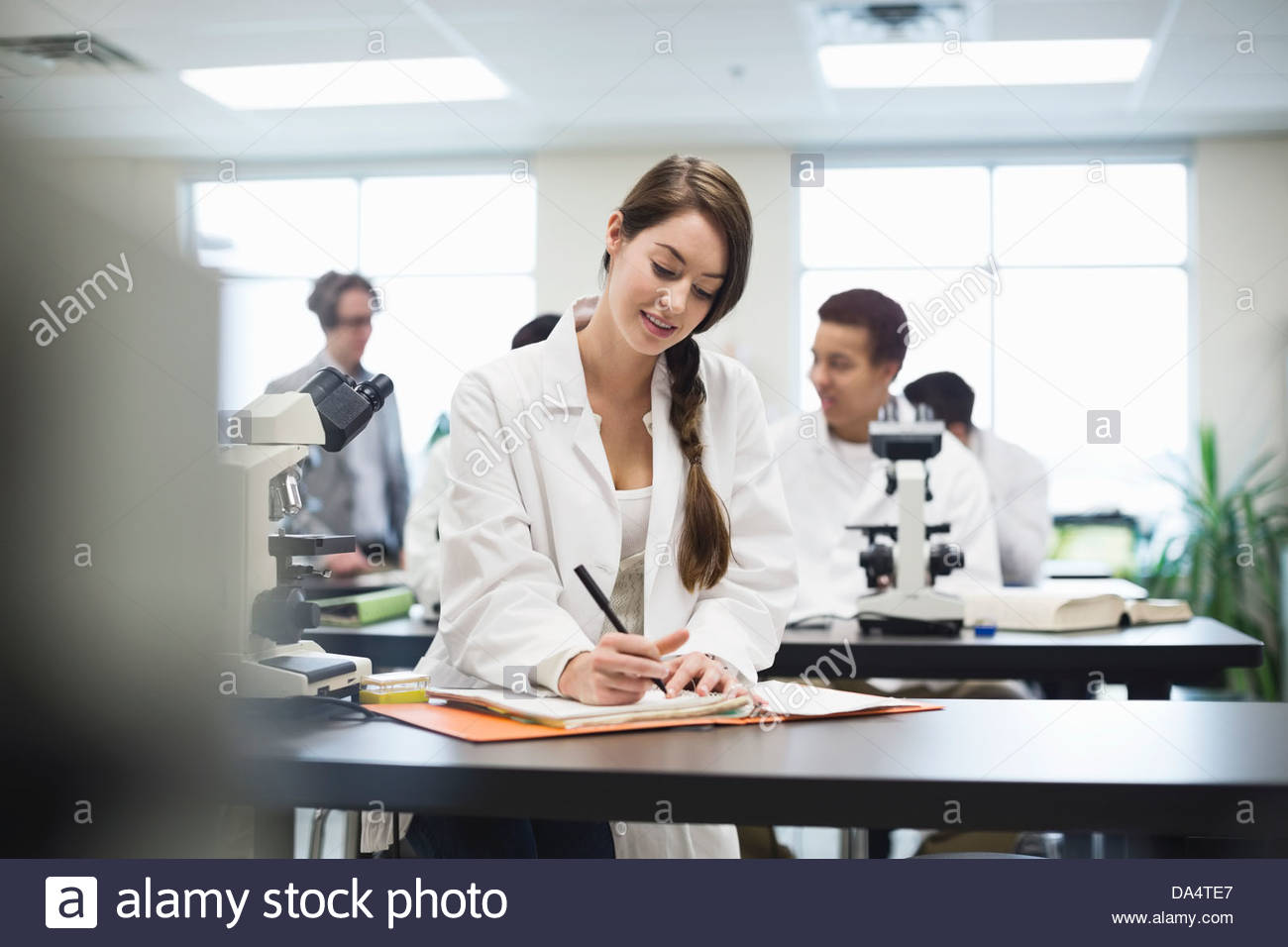 Female student writing notes in college science lab - Stock Image