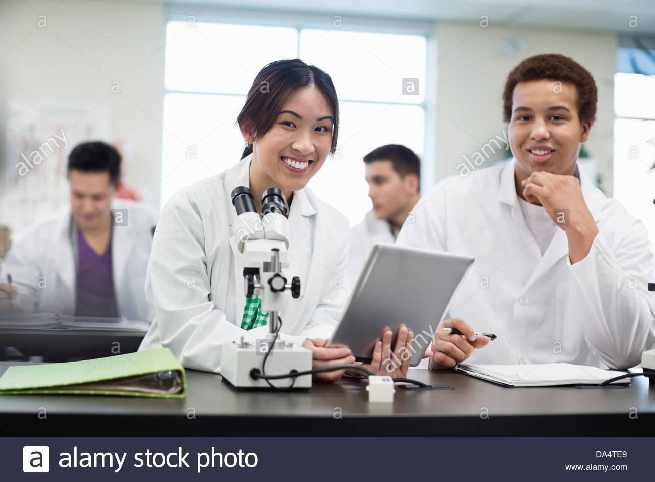 Portrait of students with digital tablet in college science lab - Stock Image