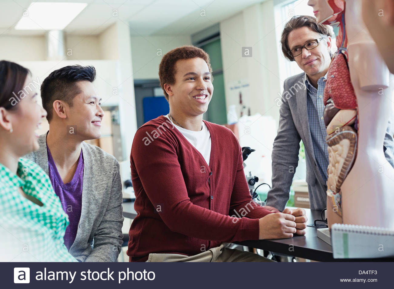 Male professor testing students about anatomy in science lab - Stock Image