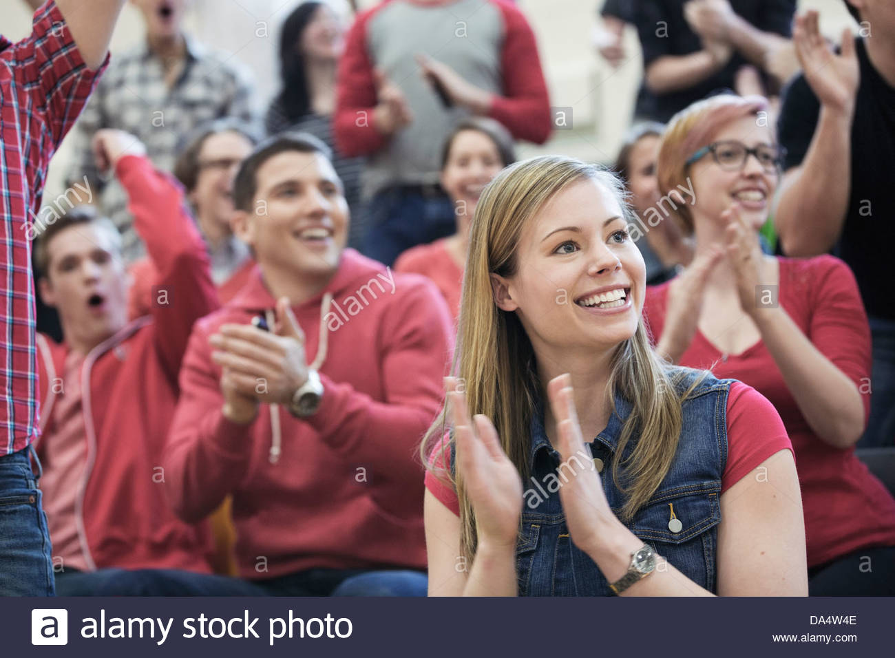Female student clapping at college sporting event Stock Photo
