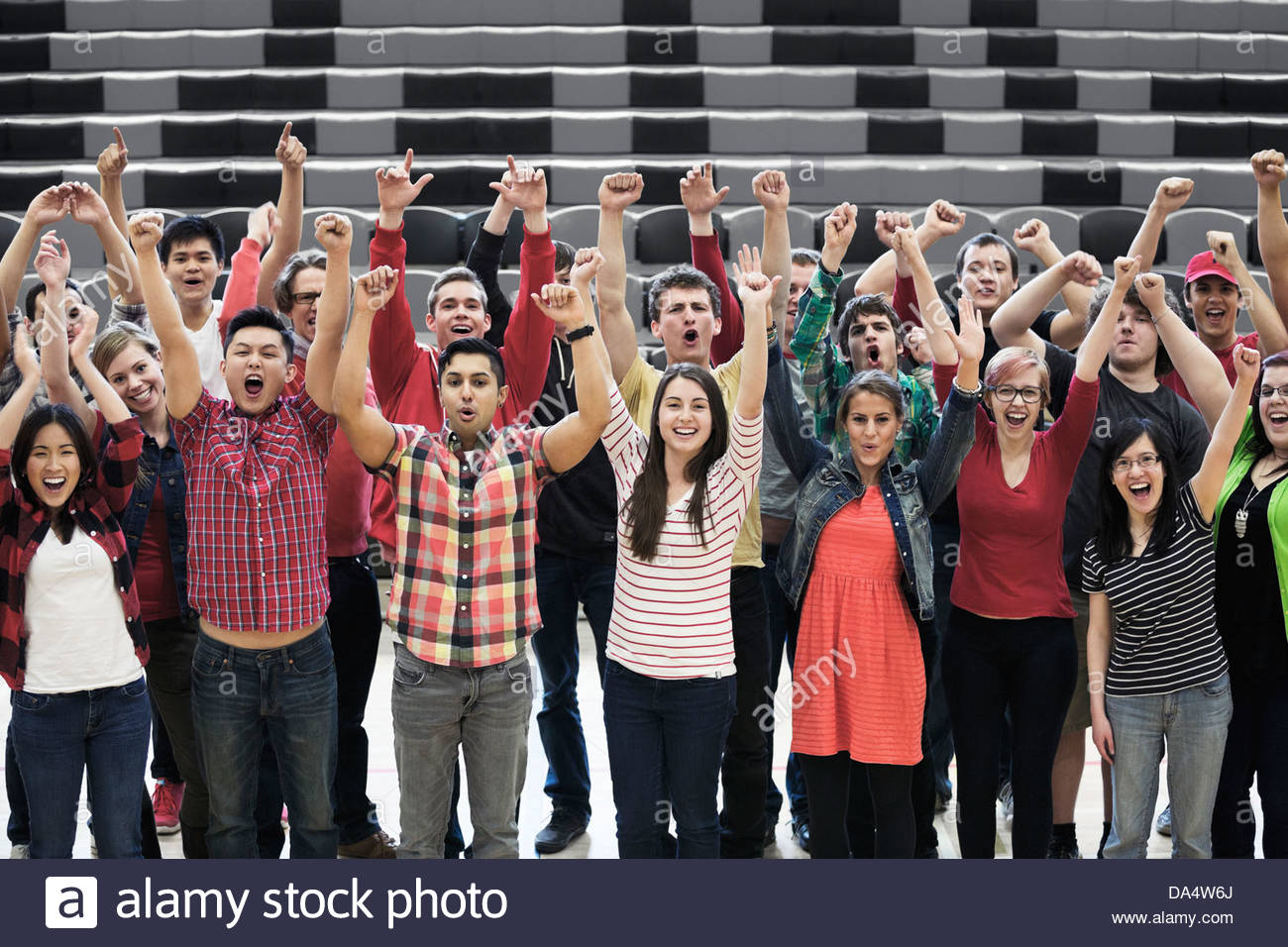 Portrait of large group of students cheering at college sporting event - Stock Image