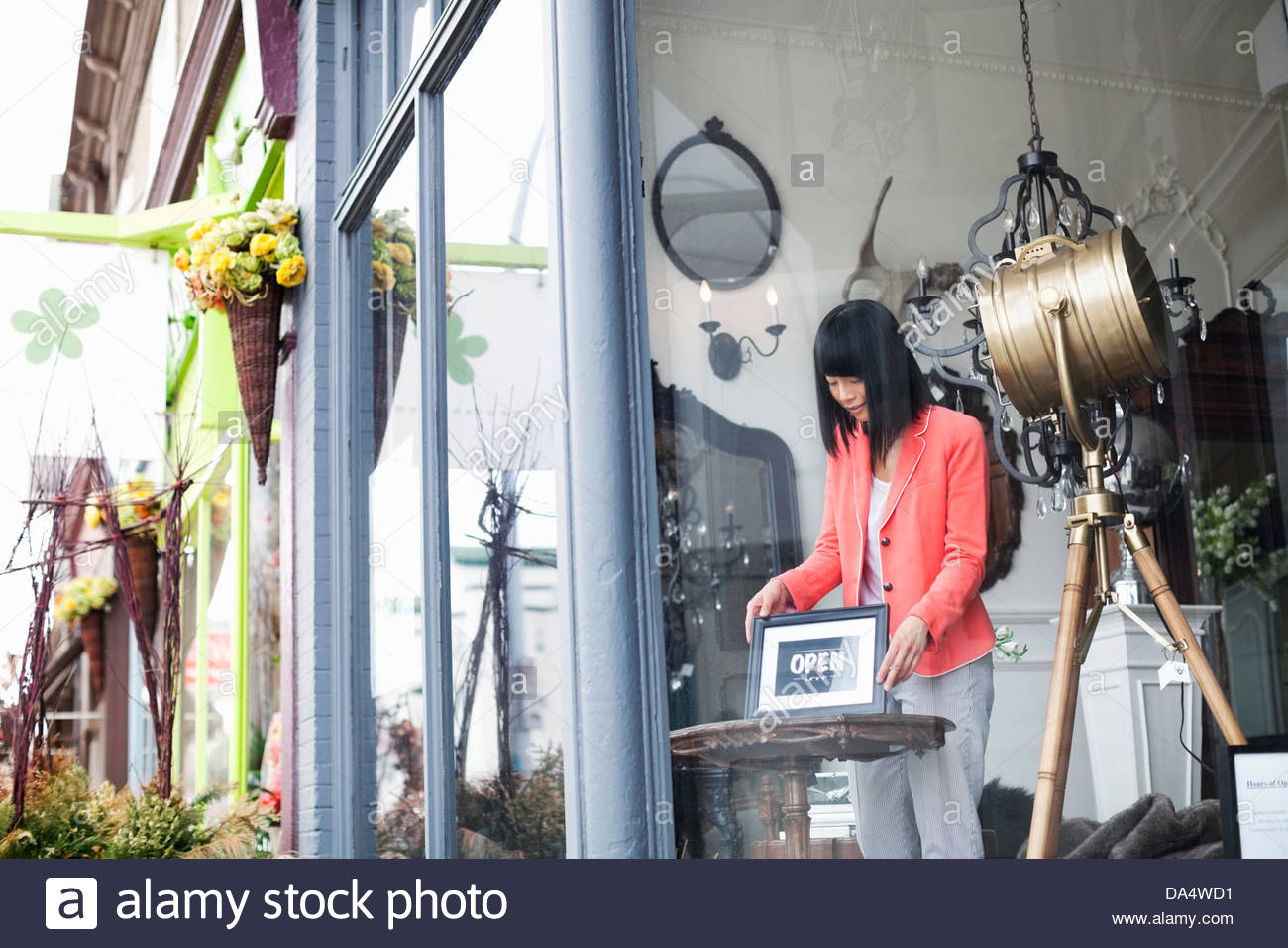 Female business owner displaying open sign in furniture store window - Stock Image