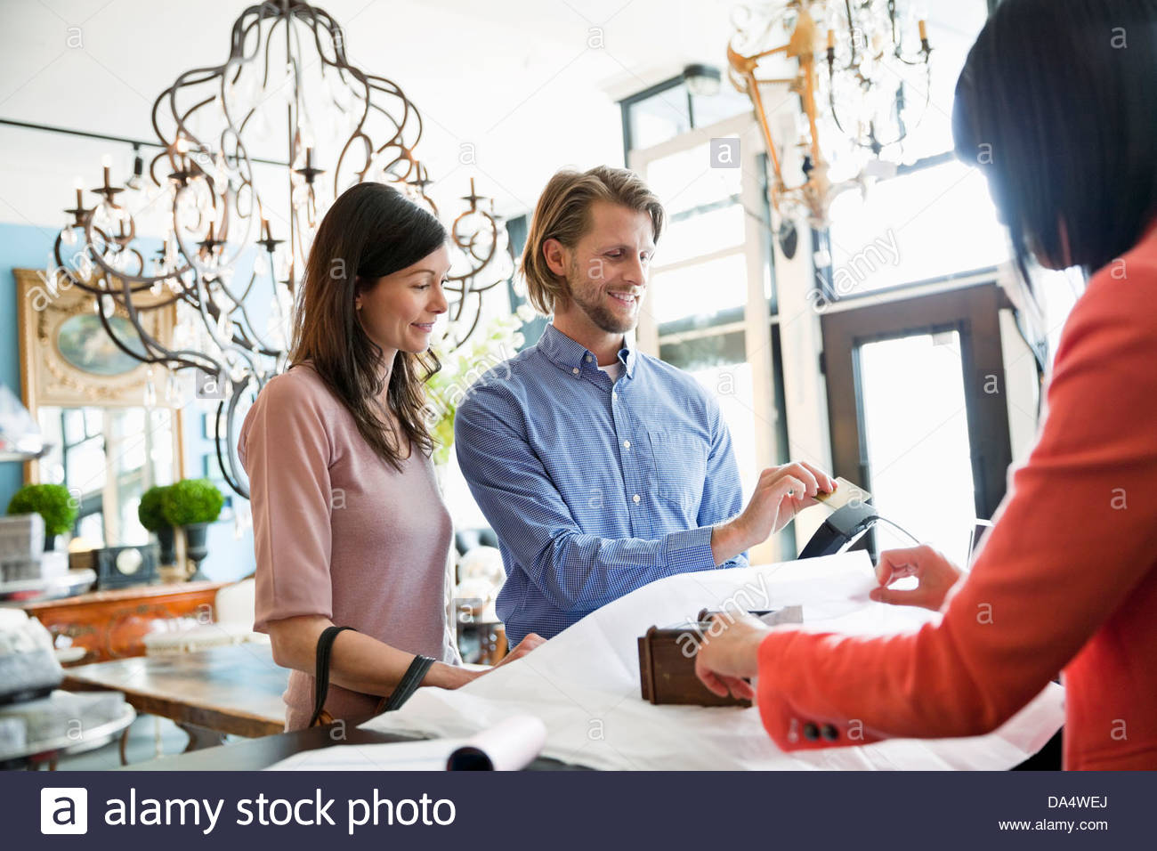 Couple paying for purchase at furniture store - Stock Image