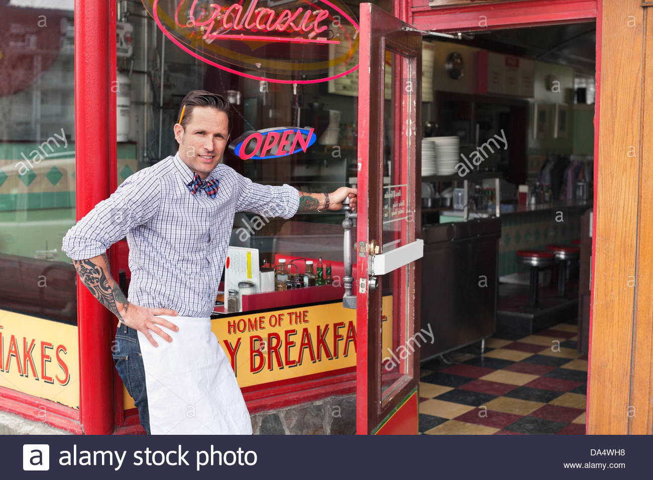 Portrait of male business owner opening diner door - Stock Image