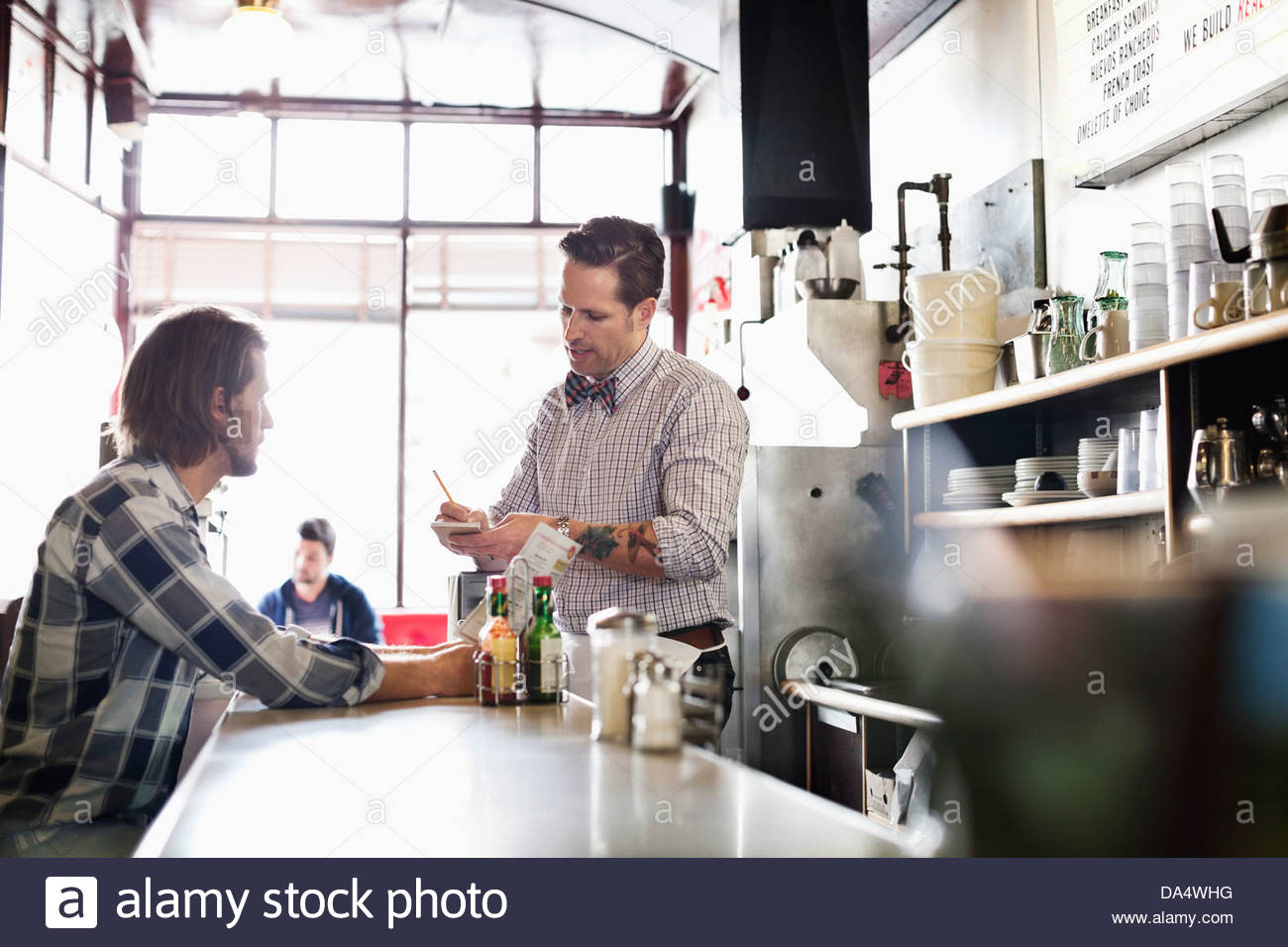 Male business owner taking customer's order at diner counter - Stock Image