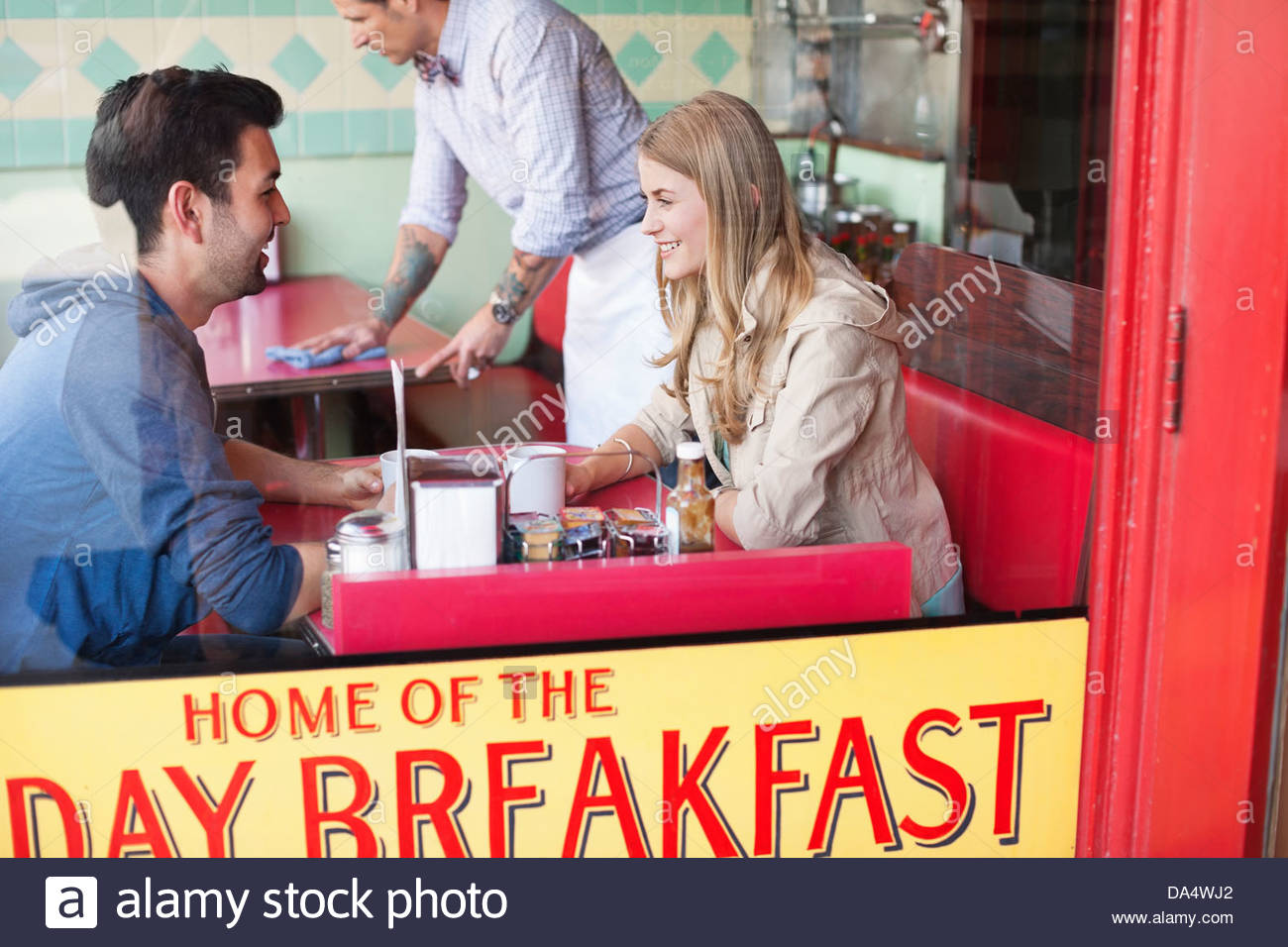 View through window of couple having coffee at diner - Stock Image