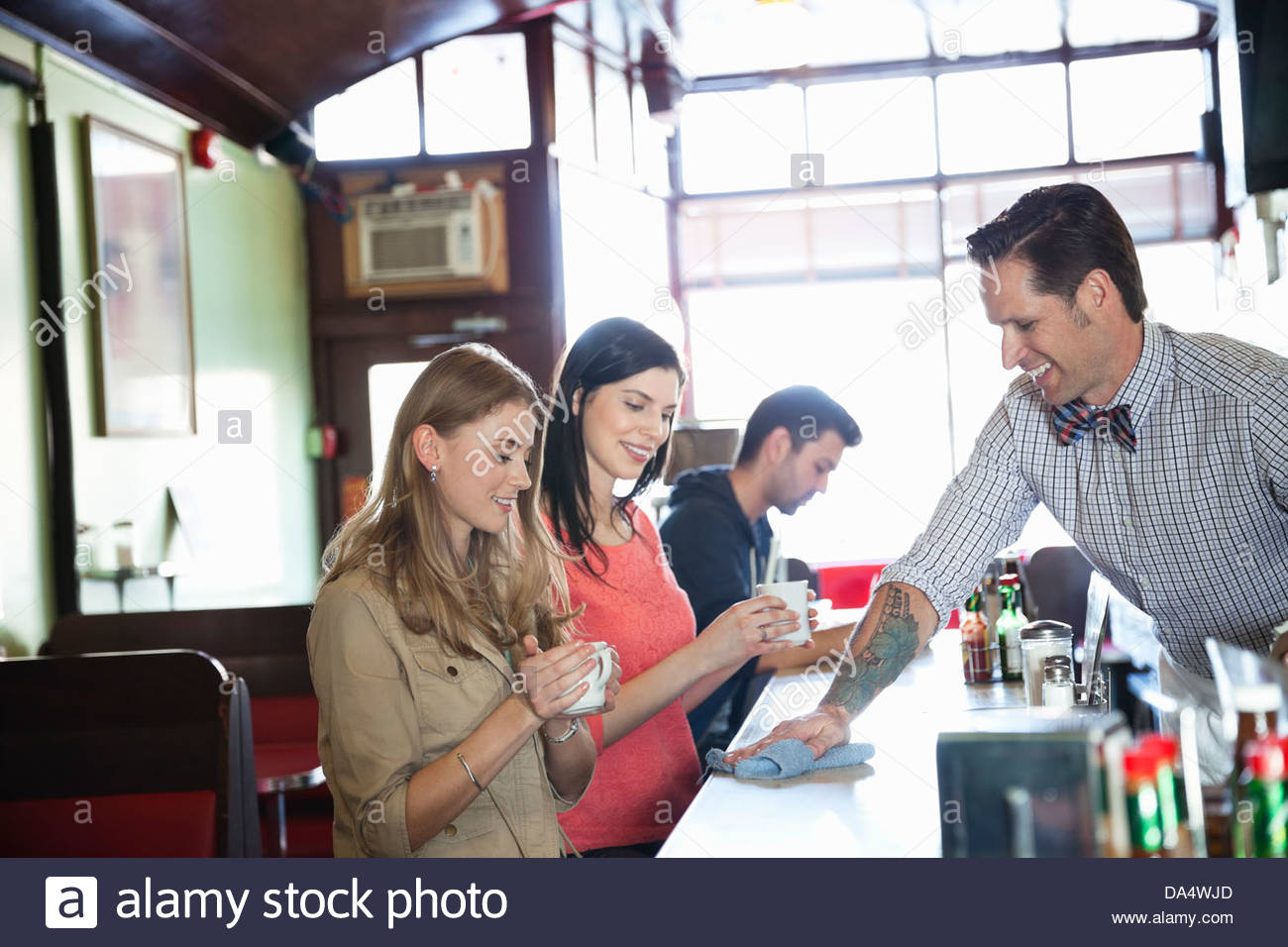 Male diner owner wiping counter for customers - Stock Image