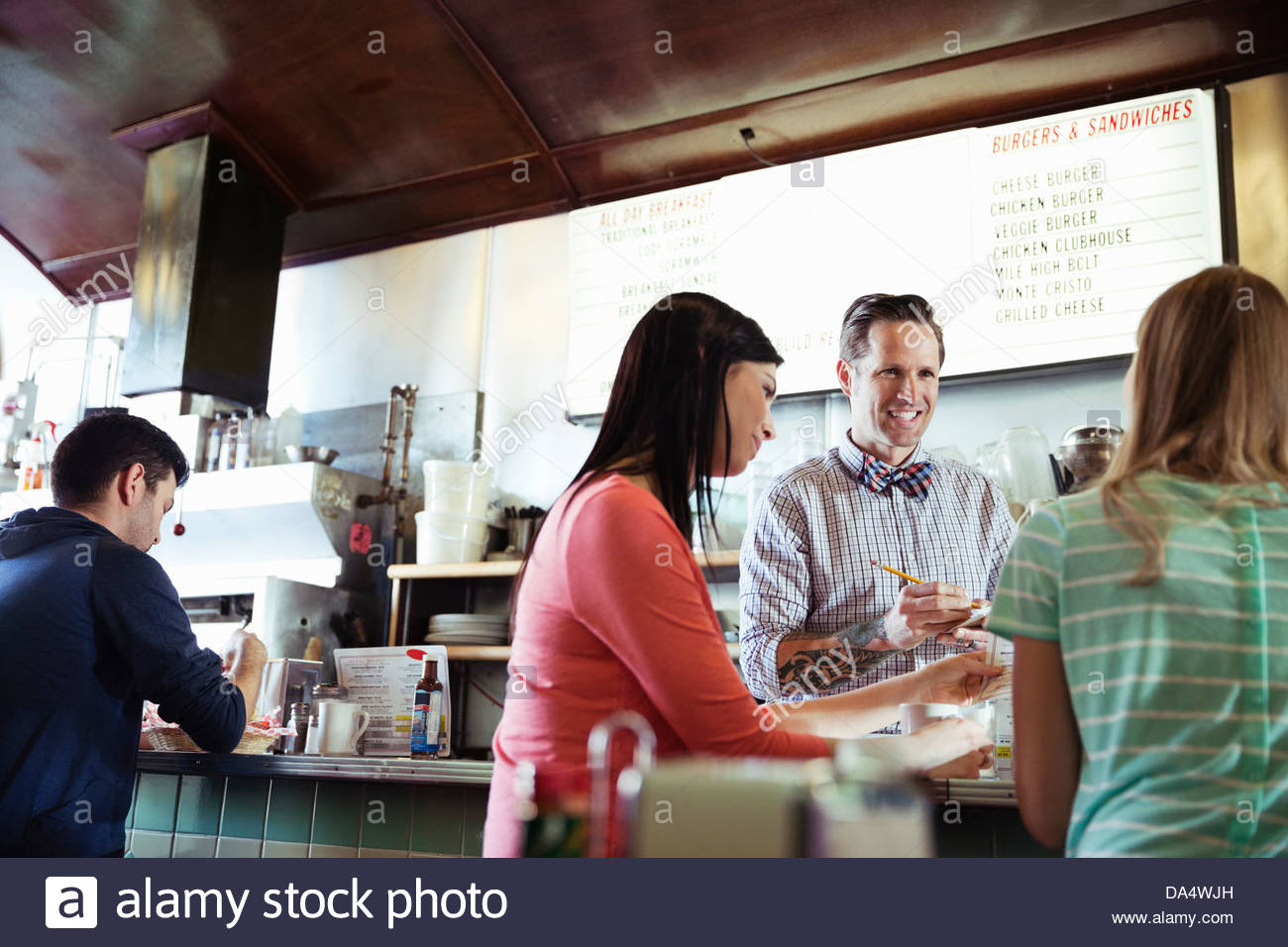 Diner owner taking customers orders at counter - Stock Image