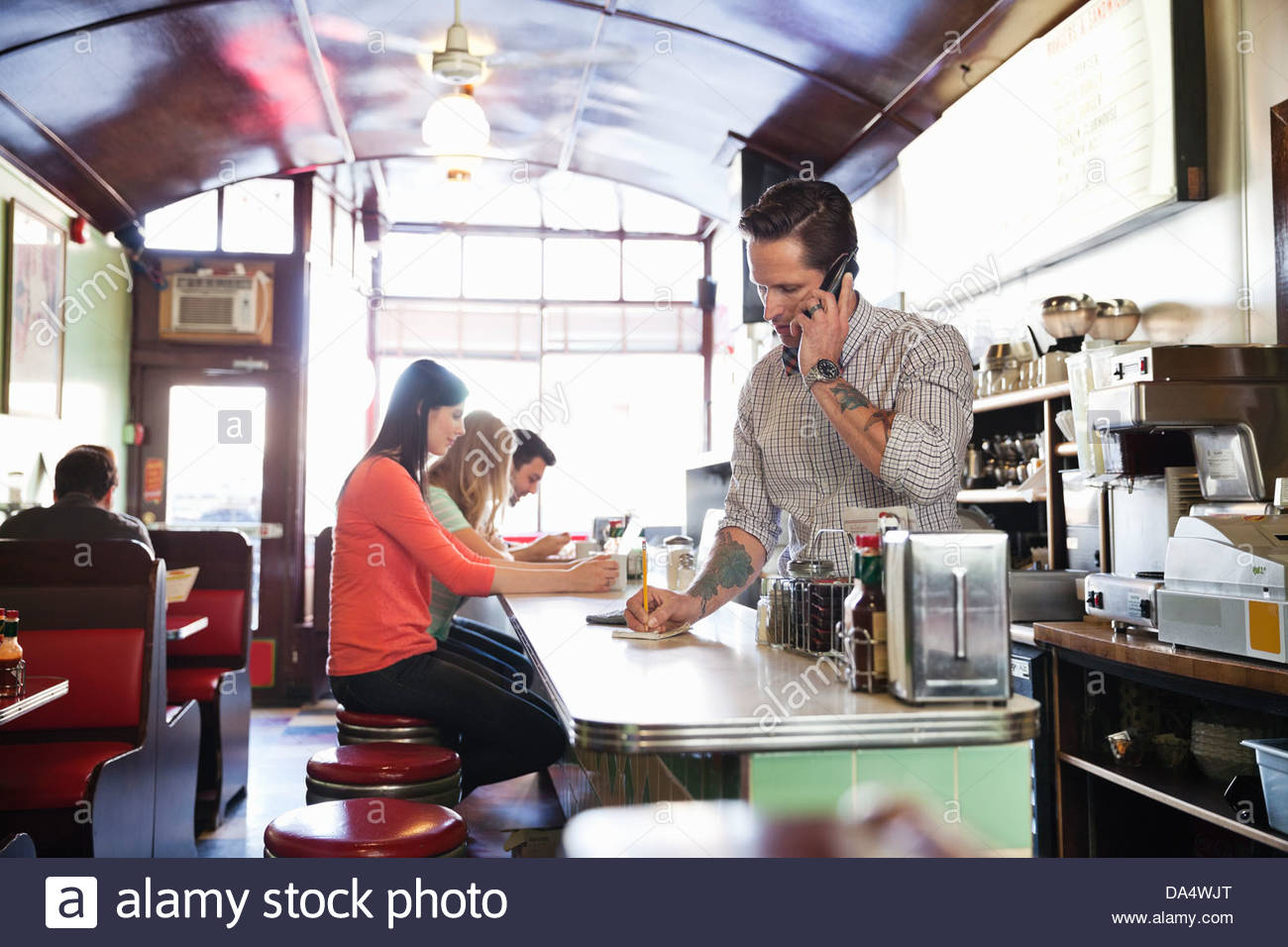 Diner owner taking order by phone at counter - Stock Image