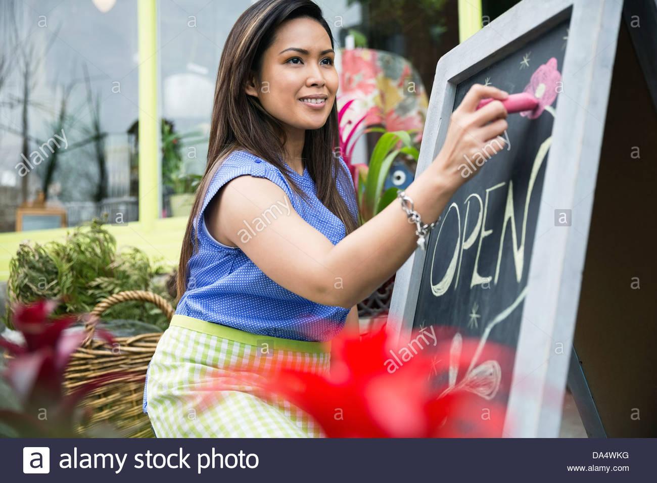Female florist drawing open sign on blackboard outside flower shop - Stock Image