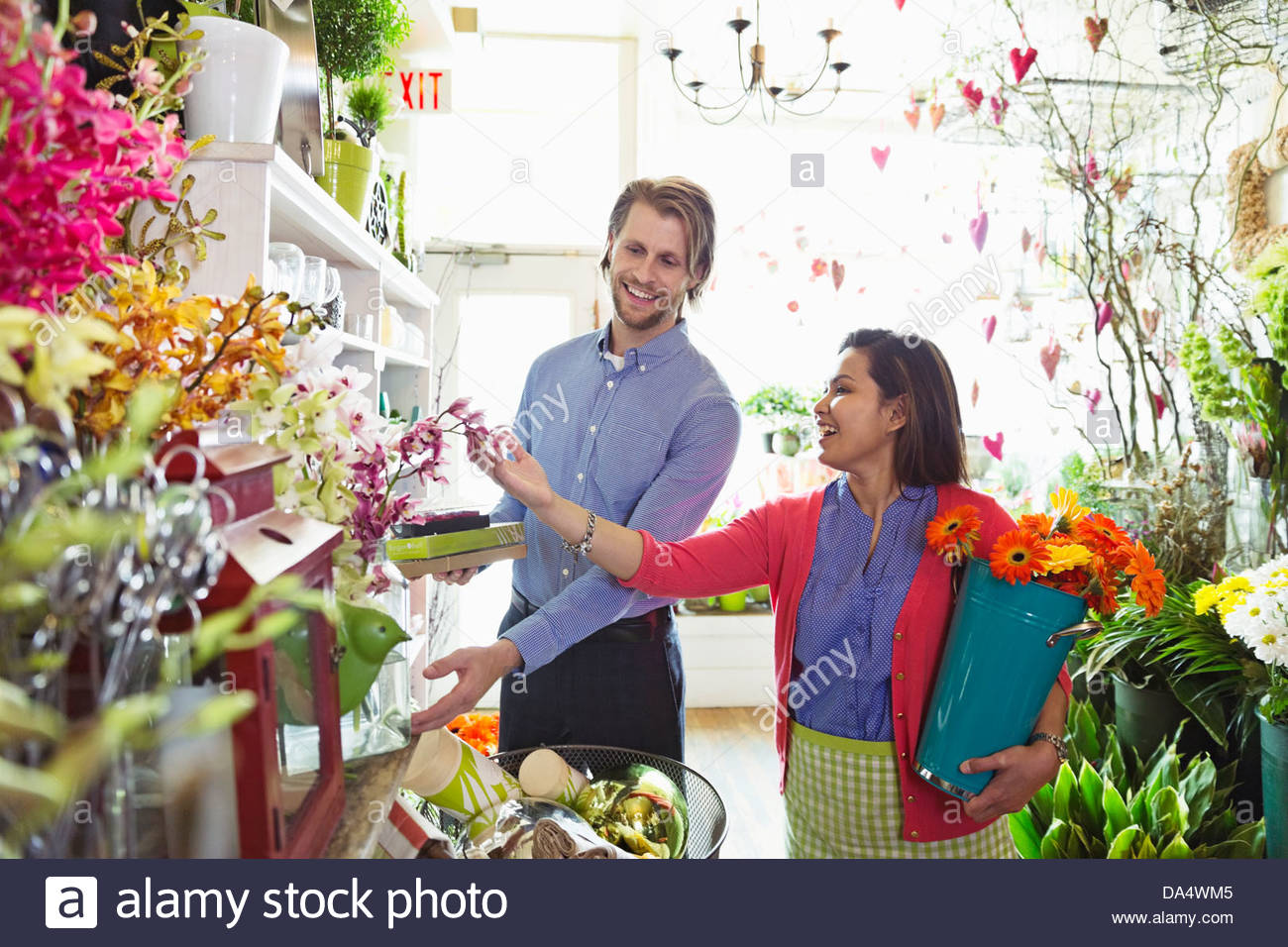 Female florist helping male customer in flower shop - Stock Image