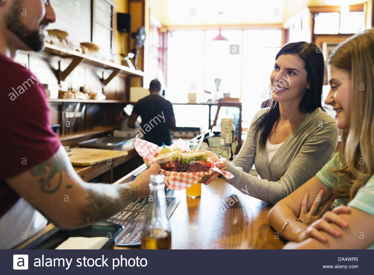 Male deli owner serving food to customers at counter - Stock Image