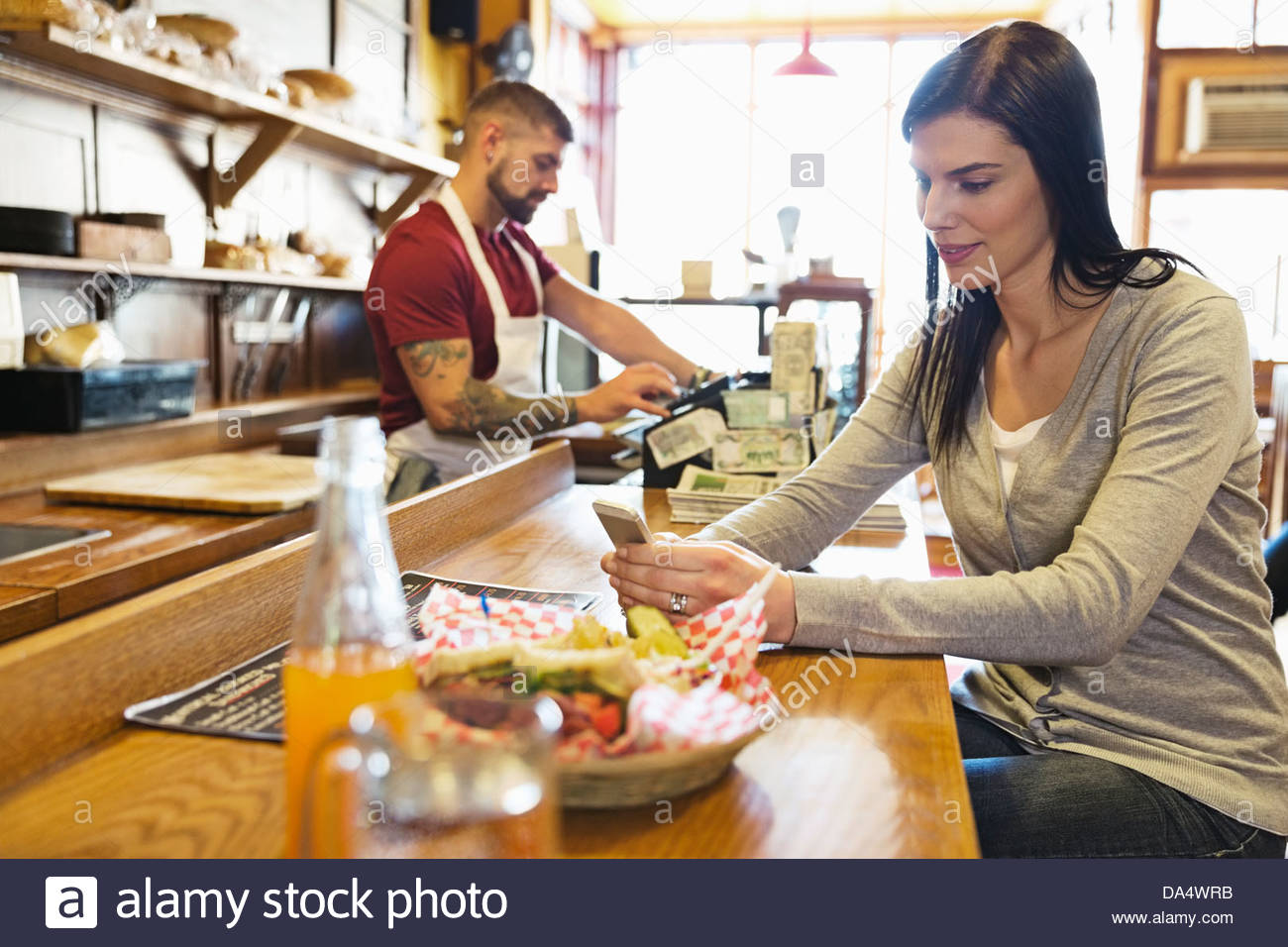 Young woman text messaging at deli counter - Stock Image