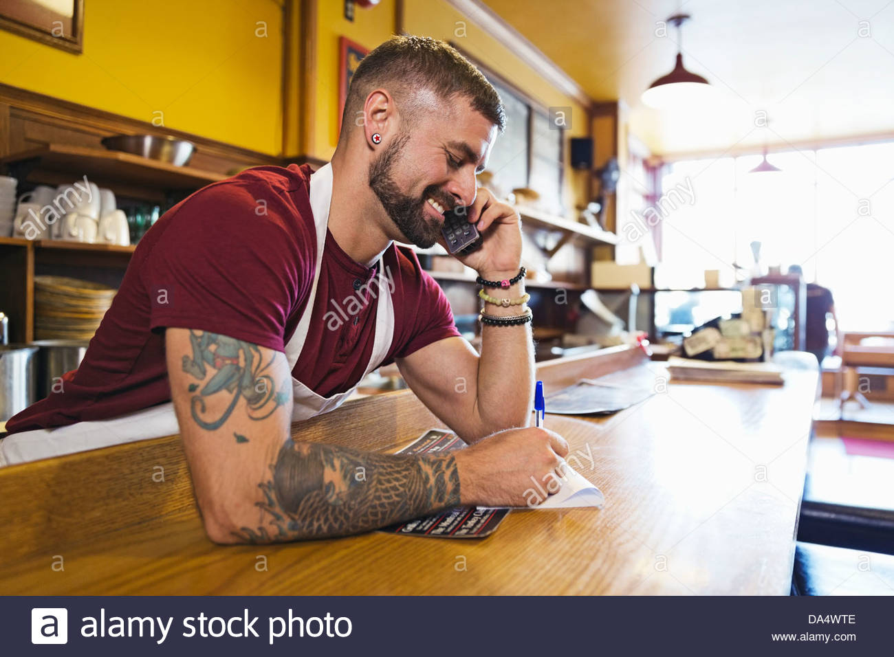 Male deli owner taking order by phone - Stock Image