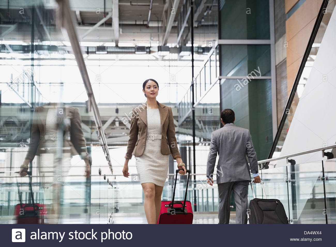 Businesswoman with suitcase walking at airport - Stock Image