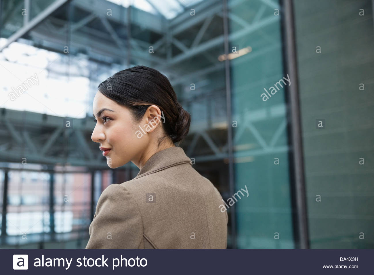 Businesswoman standing in office building - Stock Image