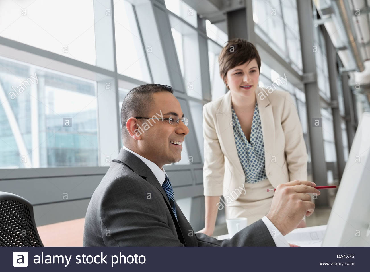 Businessman pointing to computer monitor in office building - Stock Image