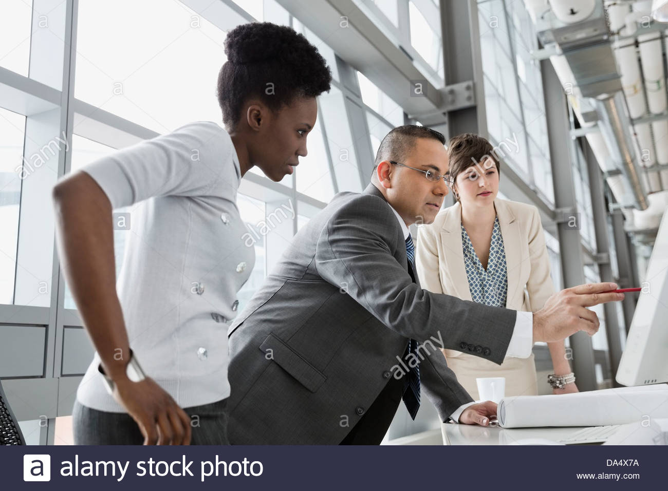 Businessman showing project on computer monitor in office building - Stock Image