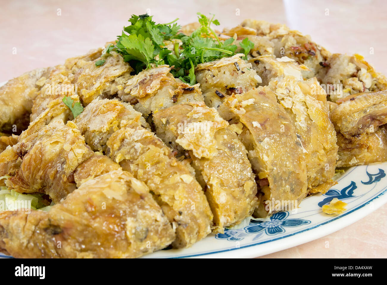 Glutinous Rice Deep Fried Stuffed Whole Chicken Chinese Dish Garnished with Cilantro Closeup - Stock Image