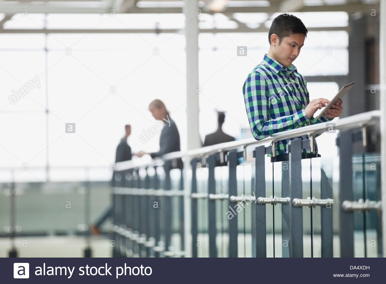 Businessman using digital tablet in office building - Stock Image