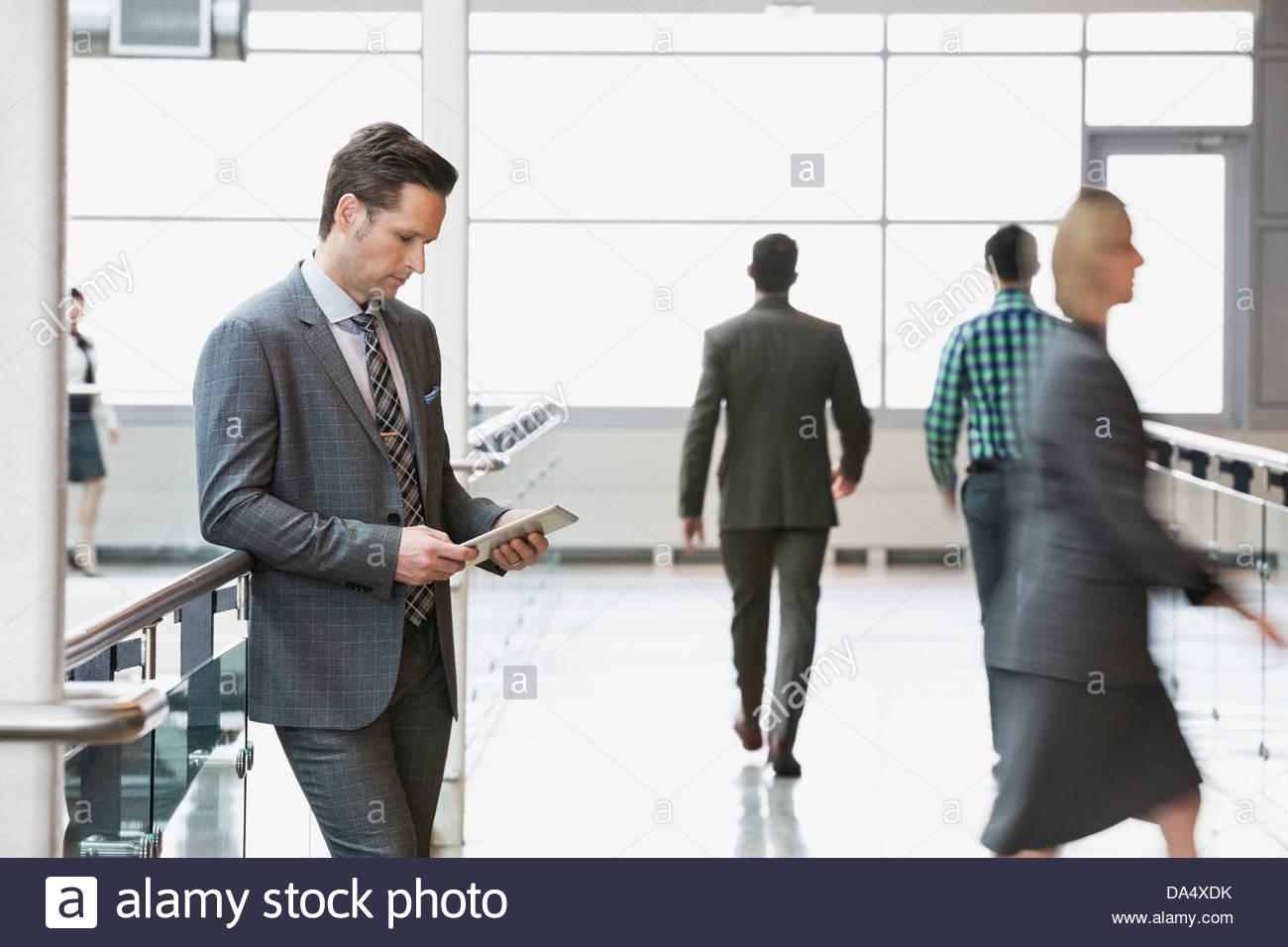 Businessman using digital tablet in office building - Stock Image