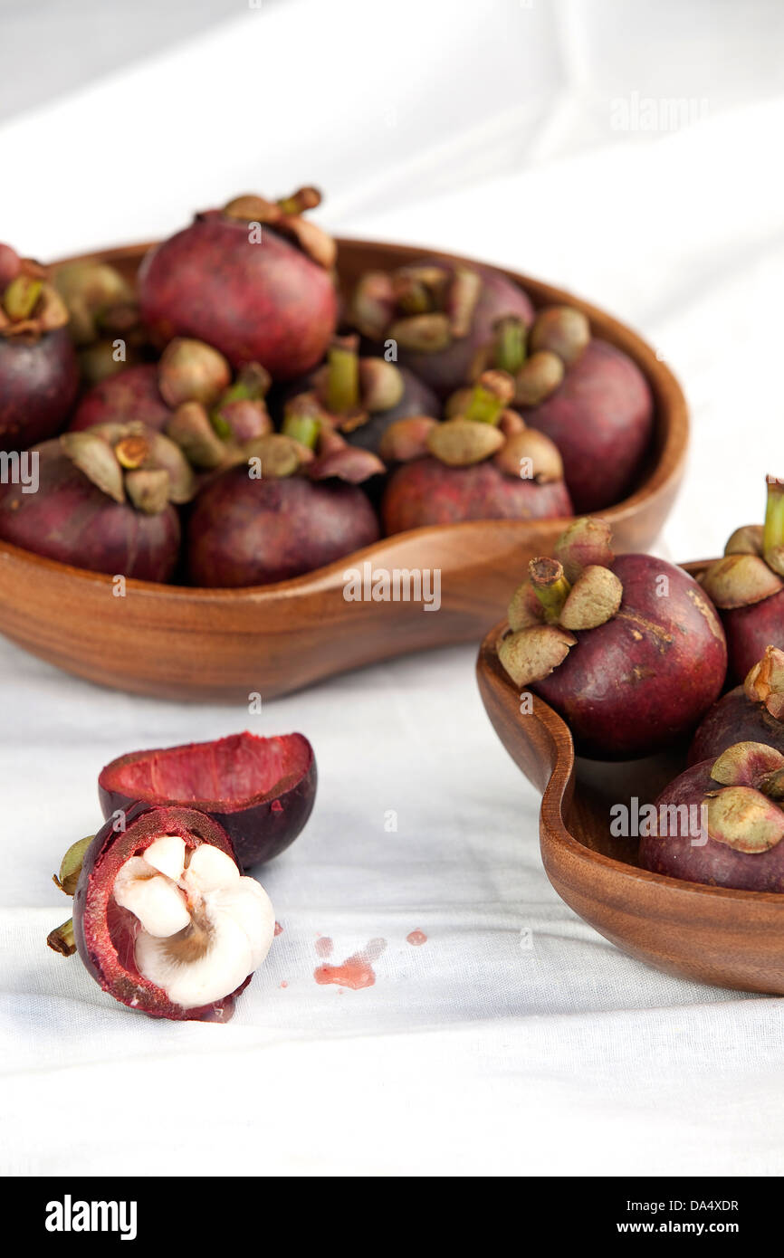 Bowls of fresh dark maroon/purple mangosteen fruits on a white surface. - Stock Image