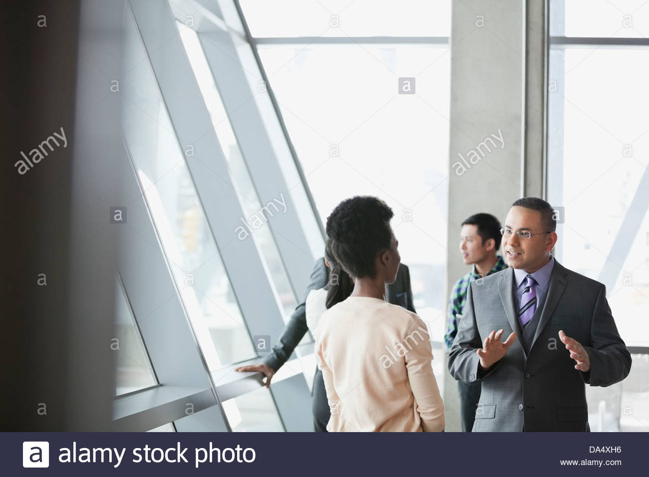 Business people talking together in office building - Stock Image