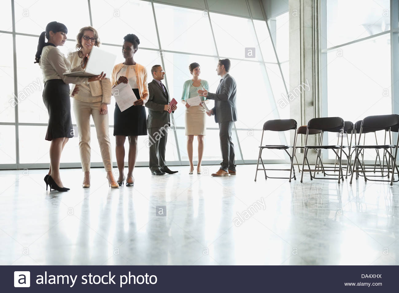 Group of business people talking together in office building - Stock Image