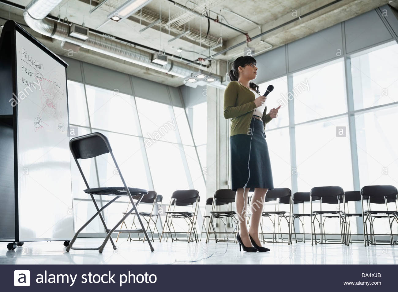 Businesswoman practicing presentation in office building - Stock Image