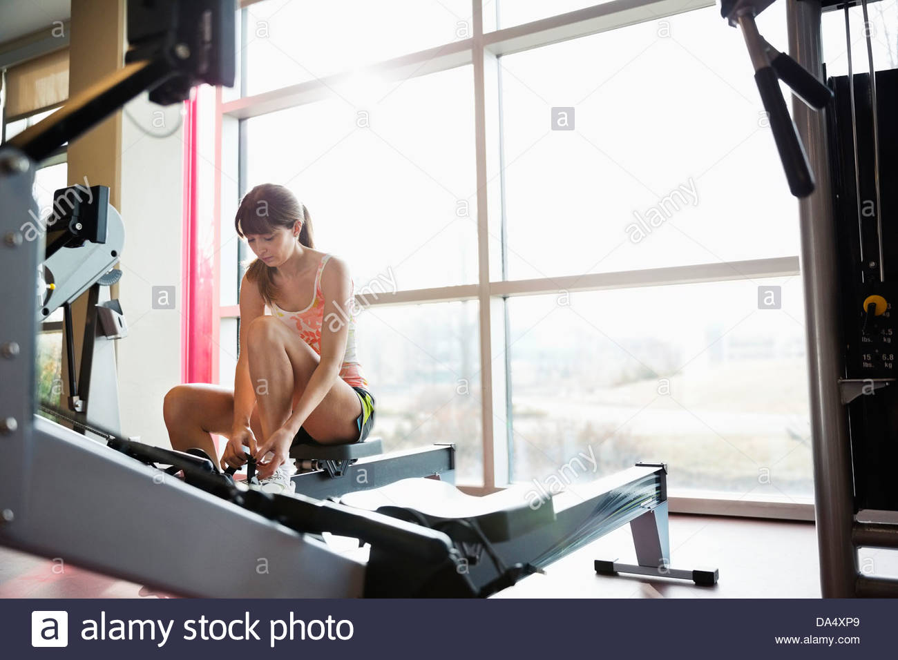 Woman preparing to exercise in fitness center - Stock Image