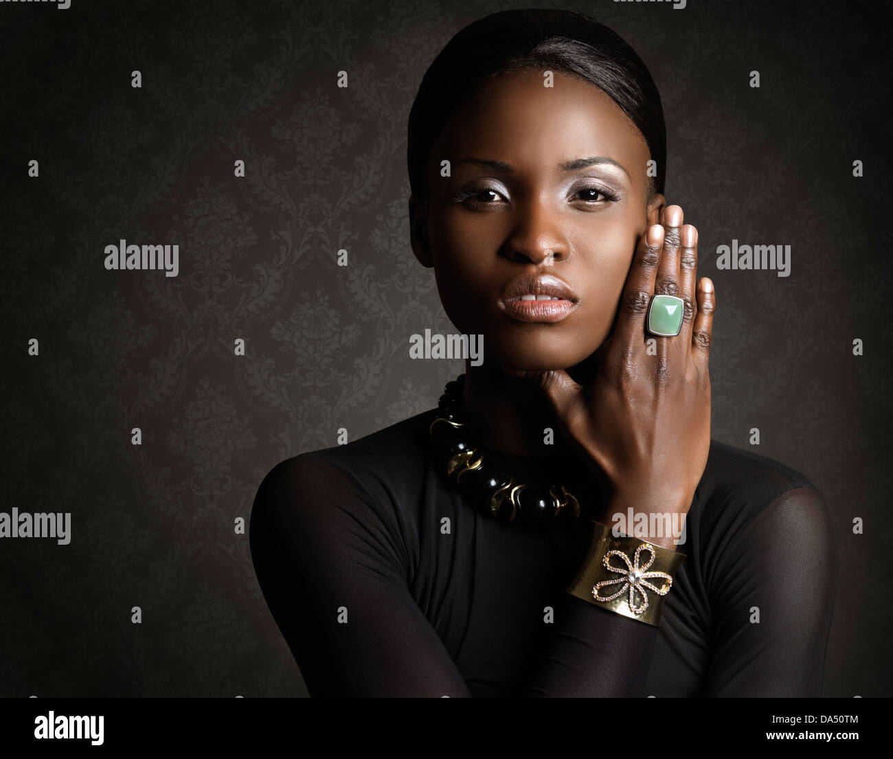 Beauty portrait of atractive african american woman in black wearing jewelry, ring, bracelet and necklace - Stock Image